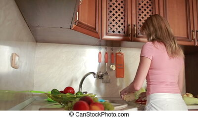 girl washes grapes vegetables on the kitchen table tomatoes...