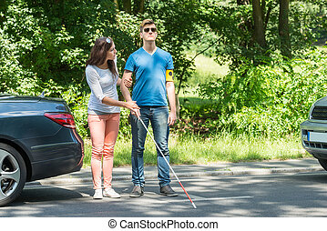 Young Woman Helping Blind Man