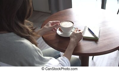 A young girl in a cafe drinking a latte - A young girl in a...