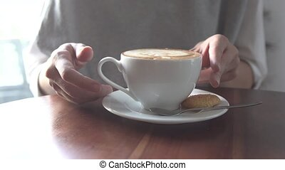 A young girl in a cafe drinking a latte. - A young girl in a...