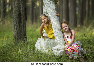 Two cute little girls sitting on an old pedestal in the Park...