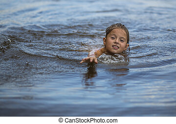 Little girl swimming in the river