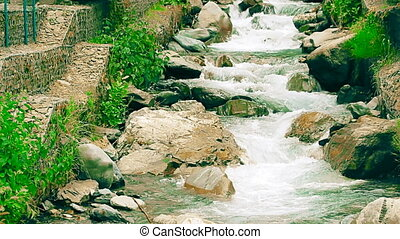 Shallow mountain river with artificial cascades made of...