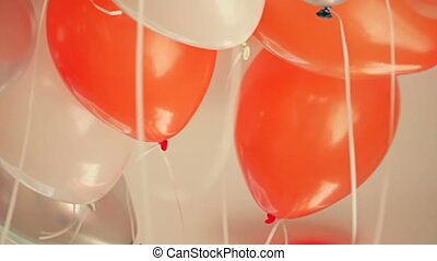 Close-up view of bright orange, silver and white balloons...