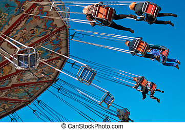 Action photo of carousel on blue sky