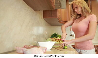 woman prepares the meat in the kitchen. home cooking dinner....