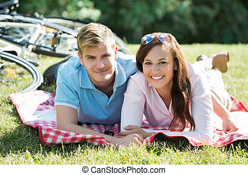 Happy Couple Laying Down On The Blanket At Park