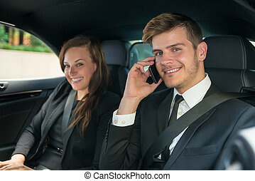 Happy Young Businessman And Businesswoman In The Car