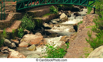 Tropical mountain river with small waterfalls and decorative bridge in the sunny day