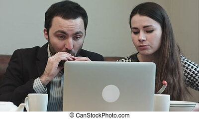 business people at lunch looking on laptop screen and...