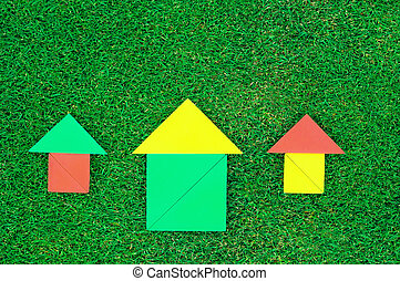 House and sun made of tangram figures on natural grass.