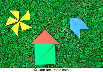 House, aircraft and sun made of tangram figures on natural...
