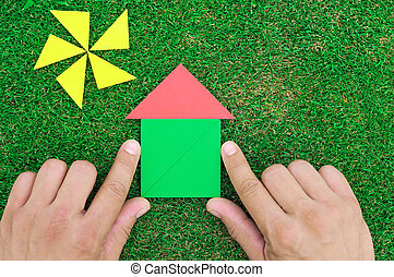 House and sun made of tangram figures on natural grass....