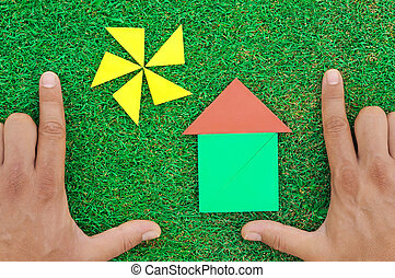 House and sun made of tangram figures on natural grass. Male...