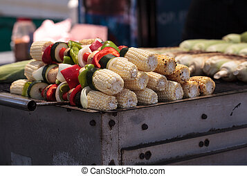 Corn, pepper and onion kabobs on a barbecue grill cooking at...