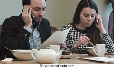 business people talking by phones at lunch break - business...