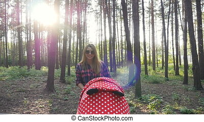 Mother with baby in buggy walking in park - Ufa, Russia. -...