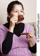 Asian woman drinking tea - Attractive senior woman drinking...