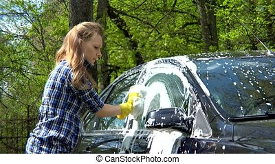 outdoor car wash with sponge. Beautiful girl washes car -...