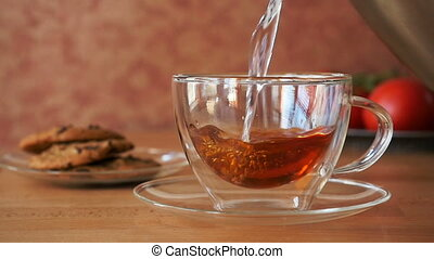 Pouring tea into a cup - Pouring tea into a glass cup on a...