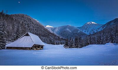 Small mountain cottage in winter valley at sunset