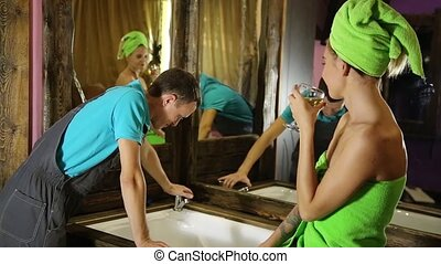 Plumber having flirt with young girl at home. men with young female customer before flirt. girl wearing a bath towel, holding a glass of white wine