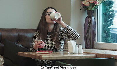 beautiful girl enjoying an hot coffee in cafe with window
