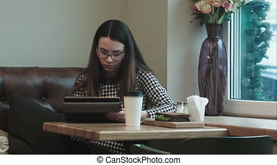 Business woman on lunch break with tablet in cafe or...