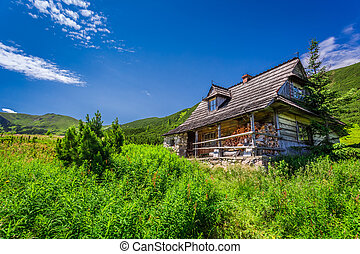 Small cottage in a mountain valley at sunrise