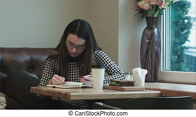 Young business woman with notebook on lunch break in cafe or...