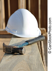 Claw Hammer and Hard Hat on Board at Construction Site