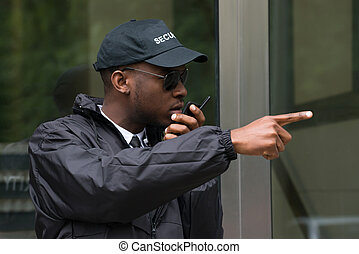 Male Security Guard Talking On Walkie-Talkie - Young Male...