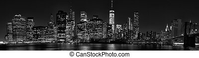 New York City Manhattan downtown skyline at dusk with skyscrapers illuminated over river panorama