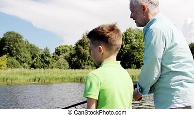 grandfather and grandson fishing on river berth - family,...