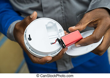 Electrician Removing Battery From Smoke Detector - Close-up...