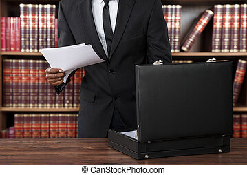 Lawyer Removing Papers From Briefcase - Close-up Of Male...