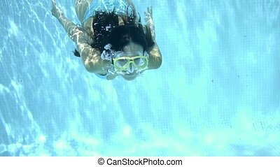 Woman in goggles swimming underwater - Single woman wearing...