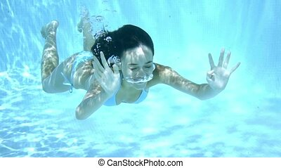 Young woman swimming underwater with closed eyes - Young...