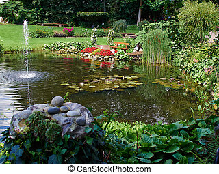 Ornamental pond and water fountain in a garden - Ornamental...