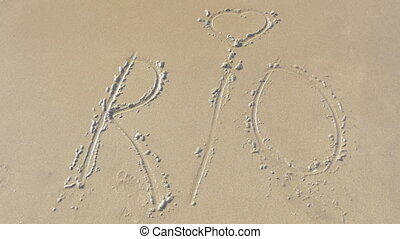 Sea wave washing Rio text from the sand - Rio with heart...