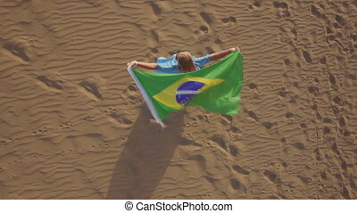 Woman with Brazilian flag waving in the wind, aerial view -...