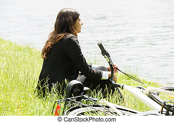 Businesswoman Sitting By Lakeside