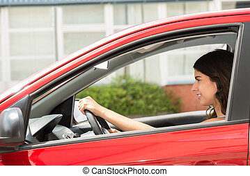 Happy Woman Driving Car - Side View Of A Young Happy Woman...