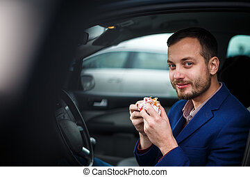 Handsome young man eating a hurried lunch in his car color...