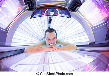 Handsome young man relaxing during a tanning session in a...