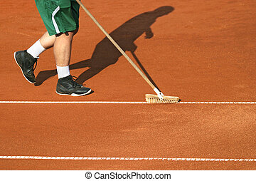 Worker cleans a line of tennis court with a brush