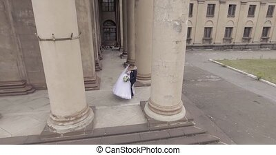 wedding couple dance between two columns aerial shot