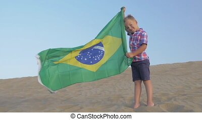 Child with flag of Brazil on the beach - Slow motion shot of...