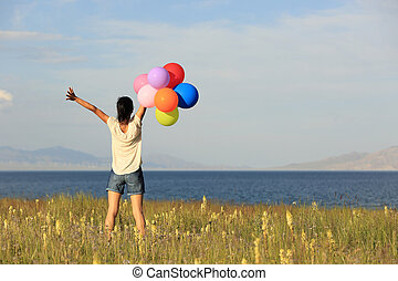 cheering young asian woman on grassland with colored...