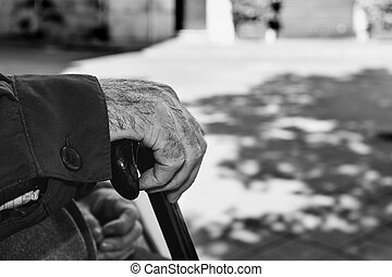 old man with a walking stick, black and white - closeup of...